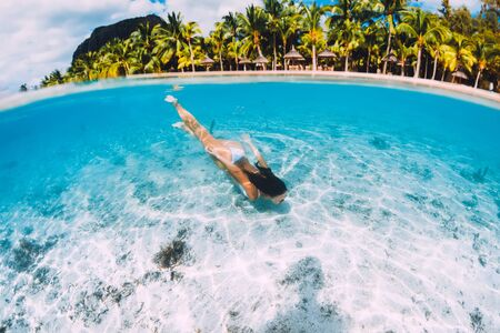 Young attractive woman swimming underwater in transparent blue ocean at Mauritius, Le Morne