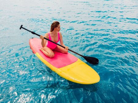 Attractive woman on stand up paddle board on a quiet blue ocean. Sup surfing in tropical sea