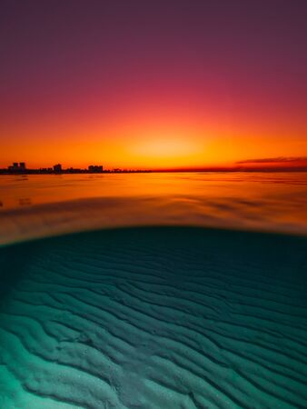 Split view with bright sunset and underwater sandy bottom.