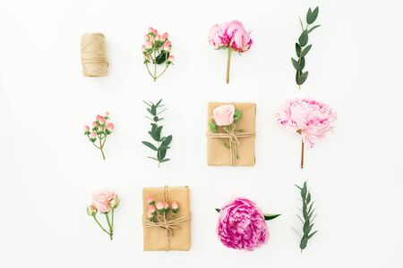 Floral composition of peonies, rose, hypericum, eucalyptus and gifts box on white background. Flat lay Stok Fotoğraf