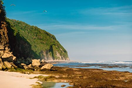 Tropical sandy beach with rocks and ocean in Bali