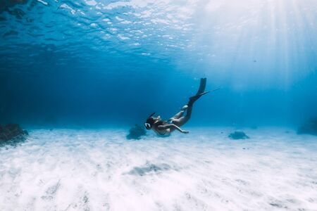 Attractive woman free diver glides with fins over sandy sea. Freediving in a tropical ocean