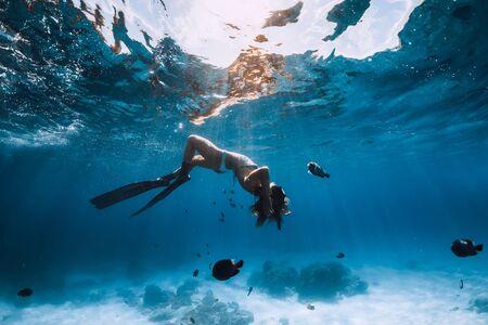Apnéiste femme avec palmes se détendre sous l'eau. Plongée en apnée et belle lumière dans l'océan