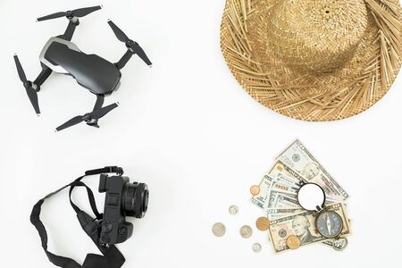 Travel holiday composition. Drone, hat, photo camera, retro compass and US cash on white. Flat lay, top view.