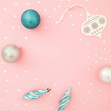 Christmas composition. Decoration and shiny confetti on pink background. Flat lay, top view.