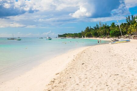 Luxury beach in Mauritius. Transparent ocean with boats, beach and coconut palms