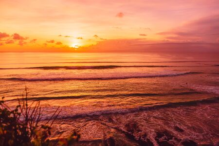 Ocean with waves for surfing and bright sunset in Bali. Stok Fotoğraf