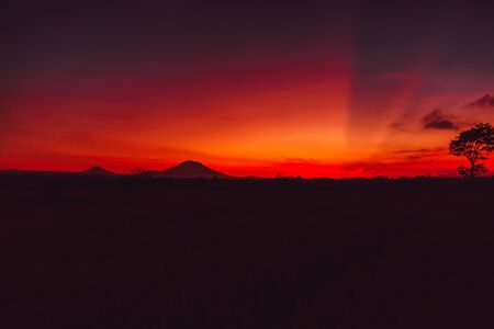 Bright colorful sunrise with silhouette of Agung volcano in Bali