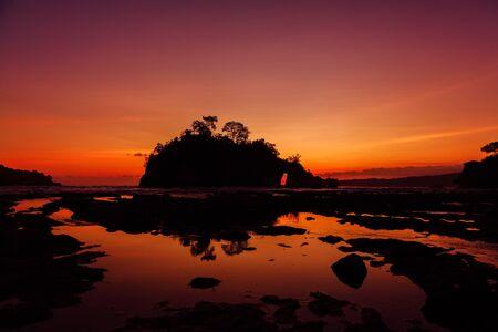Rocks island in ocean with bright  warm sunset at Nusa Penida, Bali Stok Fotoğraf