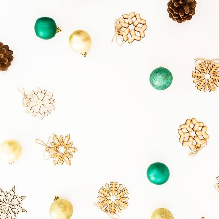 Celebration frame with Christmas balls, snowflake decorations on white background. Flat lay, top view