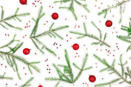 Christmas pattern of fir tree branches and red decoration on white background. Flat lay, top view