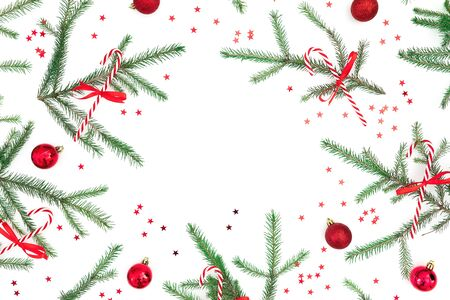 Christmas frame of fir tree branches and red decoration on white background. Flat lay, top view