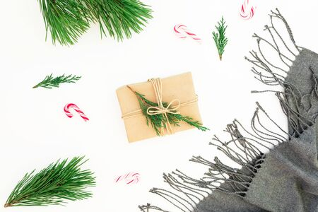 Christmas decorations with gray scarf, pine branch, candy and gift on white. Christmas, New Year concept. Flat lay, top view Stok Fotoğraf