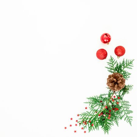 Christmas composition of pine branches and red balls on white. Flat lay, top view