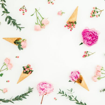 Floral spring frame with pink peonies, roses petals, eucalyptus, waffle cones on white. Flat lay