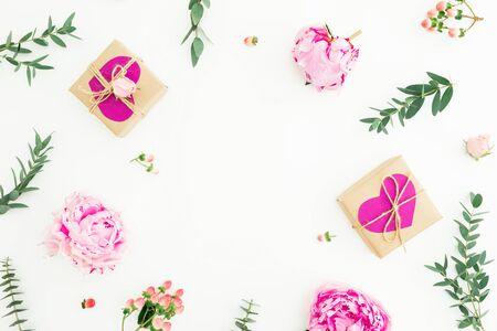 Frame of peonies, roses flowers and eucalyptus with gifts on white background. Valentines day. Flat lay, top view