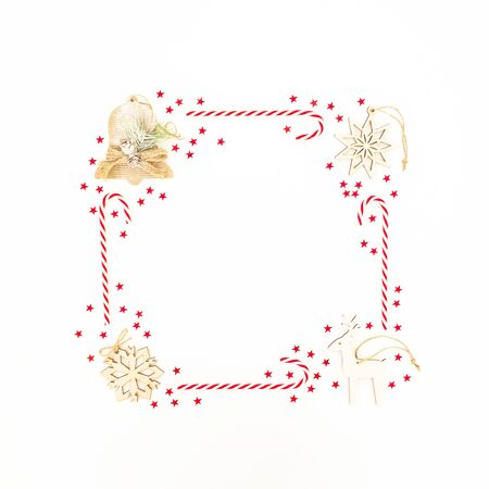 Frame made of Christmas decoration, confetti and candy canes on white background. Flat lay. New year concept