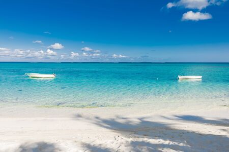 Tropical beach with transparent ocean and boats in Mauritius
