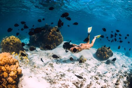 Freediver girl with yellow fins glides over sandy bottom with fishes in blue ocean