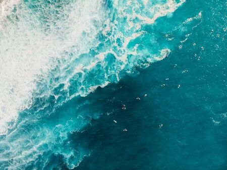 Aerial view with surfers and wave in crystal blue ocean. Top view