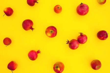 Pattern of pomegranate fuits isolated on yellow background. Food background. Flat lay, top view