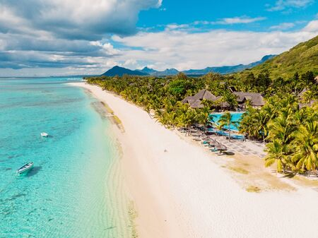 Luxury beach with mountain in Mauritius. Sandy beach with palms and blue ocean. Aerial view Stock Photo