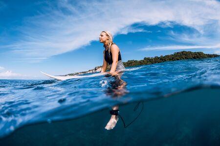 Mujer surfista sentarse en la tabla de surf y esperando la ola en el océano