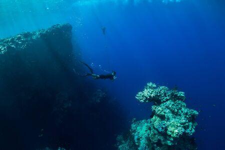 Freier Tauchgang im tiefen Ozean, Unterwasseransicht mit Felsen und Korallen. Freitauchen auf Bali