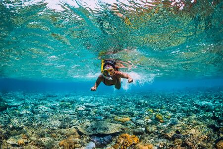 Young woman swimming underwater. Snorkeling in the tropical ocean Stock Photo