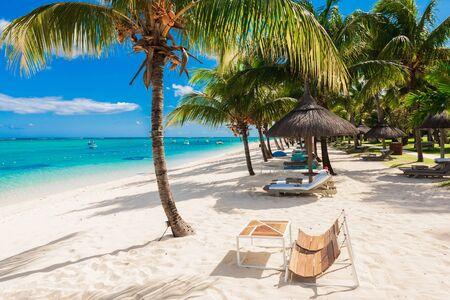 Sillas y sombrillas en Paradise Beach. Banner de vacaciones tropicales con océano Foto de archivo