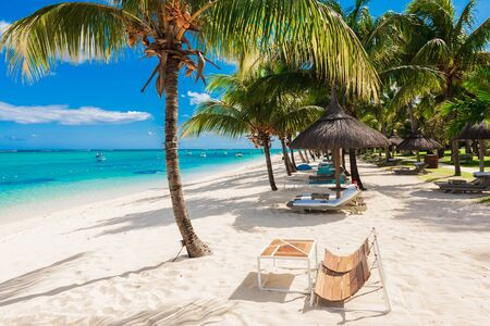 Stühle und Sonnenschirm am Paradiesstrand. Tropische Feiertagsfahne mit Ozean Standard-Bild