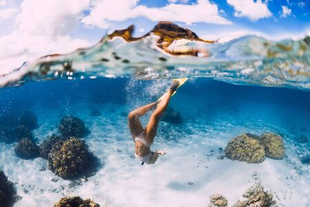 Free diver young woman with yellow fins glides over sandy bottom and corals.
