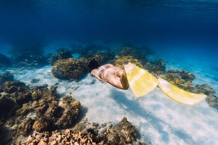 Free diver young woman with yellow fins glides over sandy bottom and corals. Stock Photo