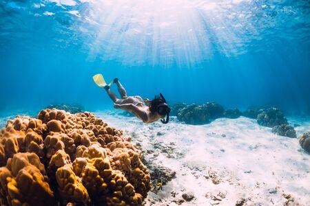 Une jeune femme apnéiste aux nageoires jaunes glisse sur le fond sablonneux et les coraux.