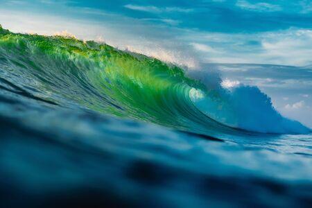 Perfekte Fasswelle im Ozean. Brechen der grünen Welle mit Sonnenlicht