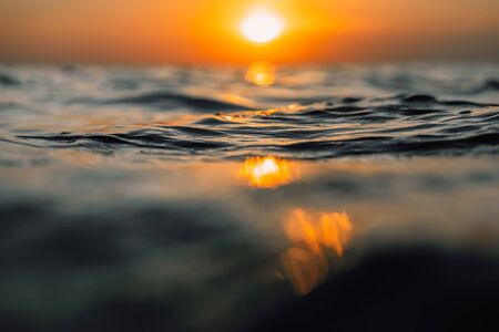 Sunset and waves in ocean. Warm water texture with bokeh