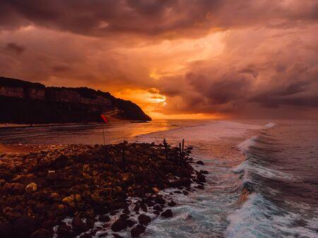 Vista aérea del océano con olas, costa y cálido amanecer. Foto de archivo