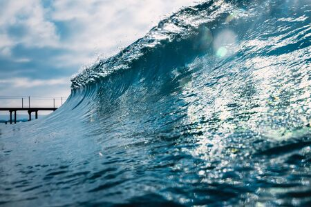 Blue crystal wave in ocean. Breaking wave and sun light