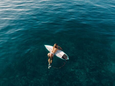 March 02, 2019. Bali, Indonesia. Aerial view of attractive surfer woman relax with surfboard in tropical ocean. Editorial