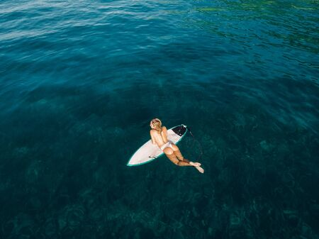 March 02, 2019. Bali, Indonesia. Aerial view of attractive surfer woman relax with surfboard in tropical ocean.