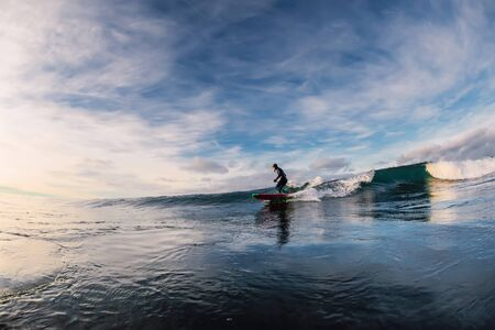 December 28, 2019. Anapa, Russia. Stand Up Paddle surfing on waves. SUP board and surfer in wetsuit in morning