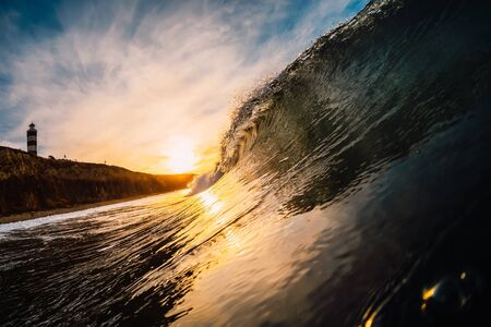 Wave in sea at sunrise. Barrel wave with warm sunrise colors and mountain with lighthouse at background Imagens