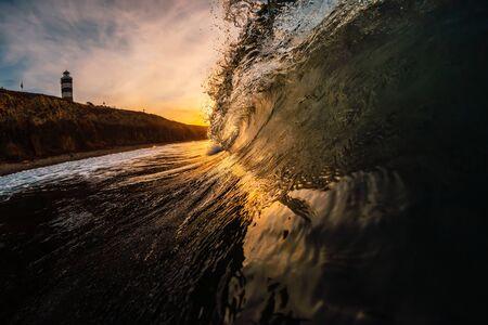 Ola en el mar al amanecer. Onda de barril con colores cálidos del amanecer y montaña con faro en el fondo