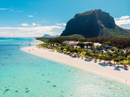 Luxury beach with mountain in Mauritius. Beach with palms and blue ocean. Aerial view Stock Photo