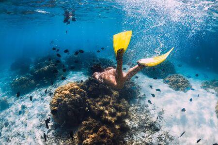 Freediver Mädchen mit Flossen gleitet über sandigen Boden im blauen Ozean
