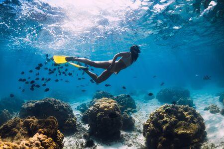 Chica apneista con aletas se desliza sobre el fondo arenoso en el océano azul