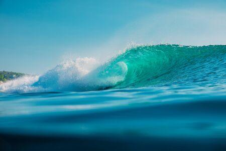 Barrel wave in ocean. Blue wave with sun light