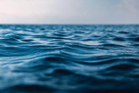 Onde blu nell'oceano. Texture acqua con bokeh Archivio Fotografico