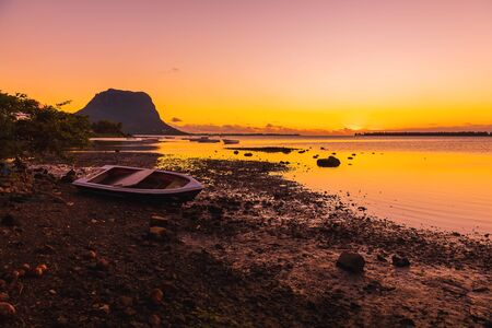 Boats and a quiet ocean at sunset time. Le Morn mountain in Mauritius.