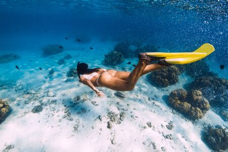 Woman glides underwater with yellow fins over sandy sea and corals.